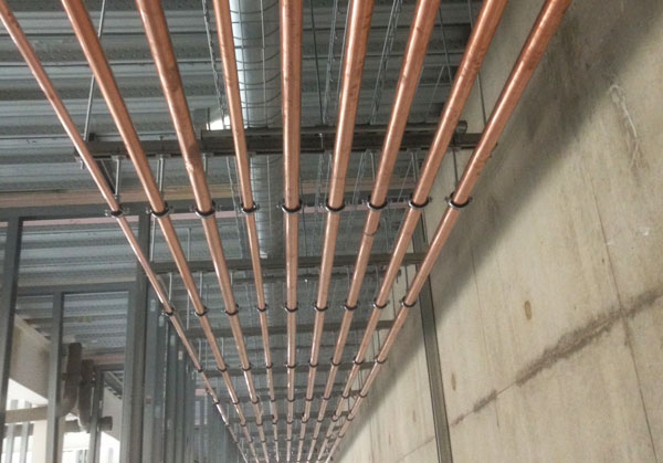 Commercial plumbing showing copper pipes in roof of building